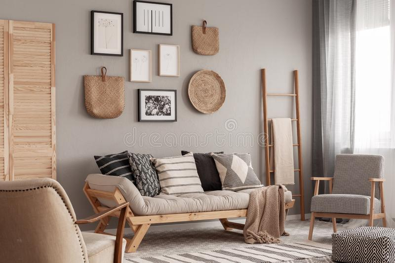 Trendy vintage armchair next to chic scandinavian sofa with pillows in classy living room interior. Trendy vintage armchair next to chic scandinavian sofa with stock photos