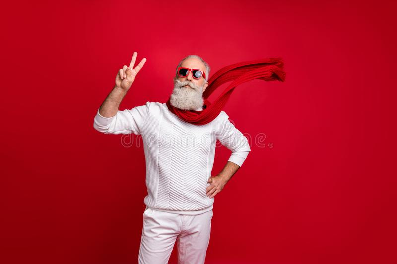 Trendy well-dressed santa character style showing v-sign wear sun specs knitted clothes isolated red background. Trendy well-dressed, santa character style stock photo