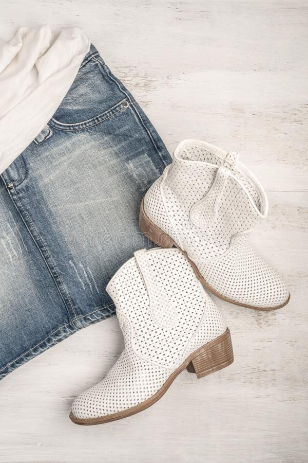 Trendy white boots and jean skirt on a wood. En background with copy space royalty free stock photos