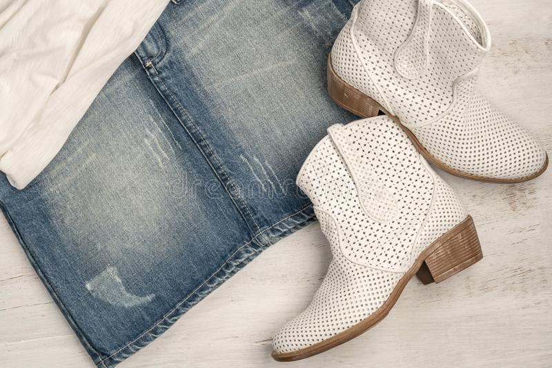 Trendy white boots and jean skirt on a wood. En background royalty free stock photo