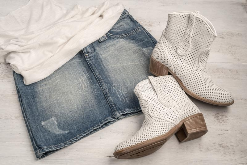 Trendy white boots and jean skirt on a wood. En background stock photos