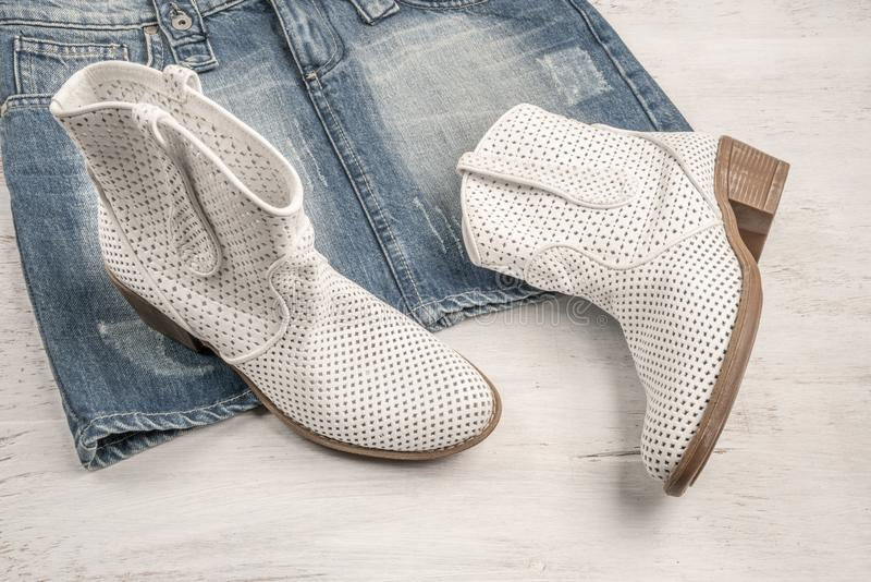 Trendy white boots and jean skirt on a wood. En background with copy space stock image