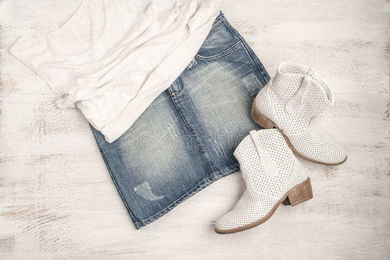 Trendy white boots and jean skirt on a wood. En background with copy space royalty free stock image