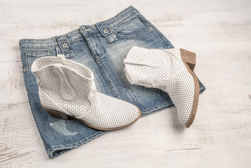 Trendy white boots and jean skirt on a wooden background. With copy space stock images