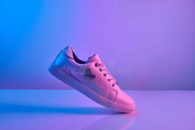 Trendy white teenage sneakers in trendy neon light. Shoe in retro surreal red, blue gradient light. Creative minimalism. Close up royalty free stock photography