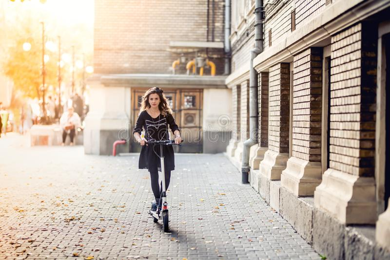 Trendy woman, beautiful brunette girl riding electric scooter in city. Trendy woman, beautiful brunette girl riding electric scooter in modern city royalty free stock photo