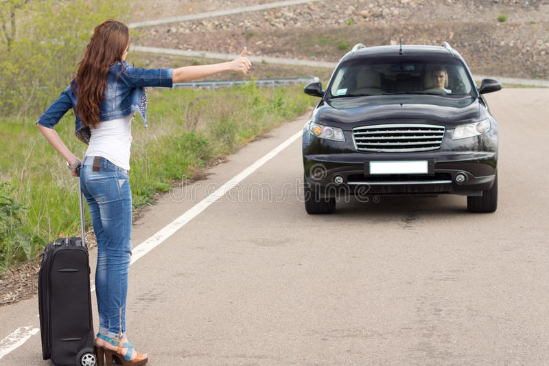 Trendy woman hitchhiking on a country road. Trendy women hitchhiking on a country road with her suitcase after breaking down at the roadside stepping into the stock photography