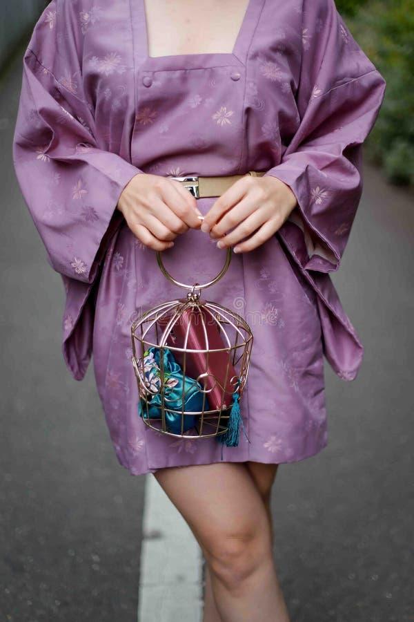 Trendy Woman holding a cage handbag wearing a mini kimono royalty free stock photography