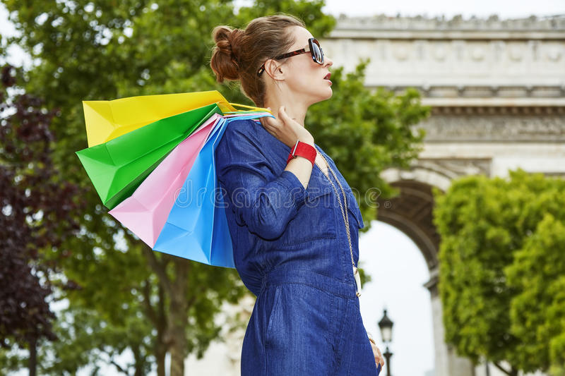 Trendy woman with shopping bags looking aside in Paris, France stock photography