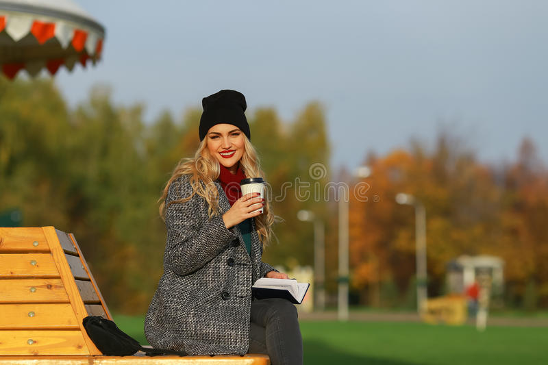 Trendy woman in stylish coat sitting on the bench in city park. Young beautiful woman smiling. stock photo