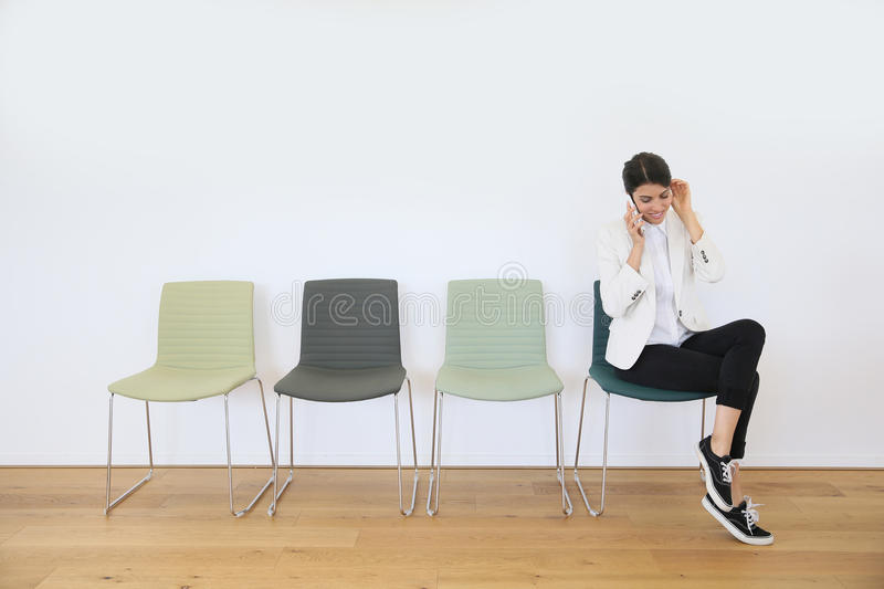 Trendy woman in waiting room on the phone stock image