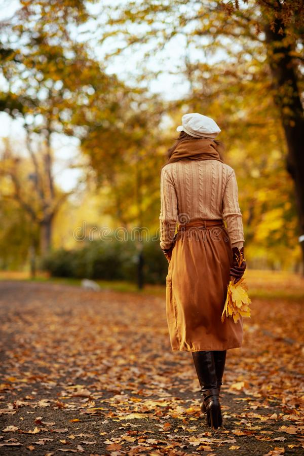 Trendy woman with yellow leaves walking outside in autumn park stock image