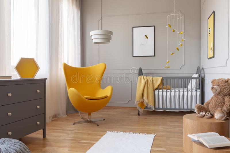 Trendy yellow egg chair in elegant grey nursery with wooden crib and posters on the wall royalty free stock photography