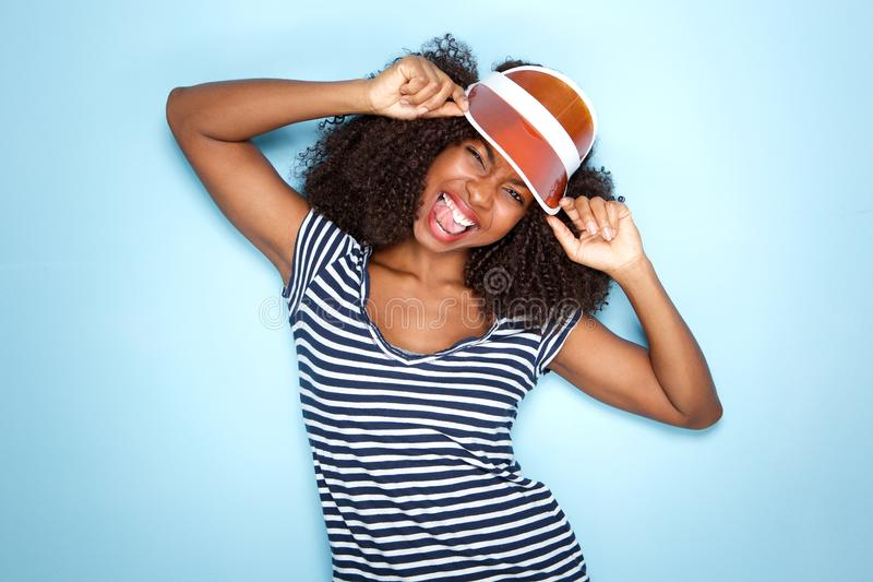 Trendy young african woman in cap sticking out tongue over blue background. Close up portrait of trendy young african woman in cap sticking out tongue over blue royalty free stock photo