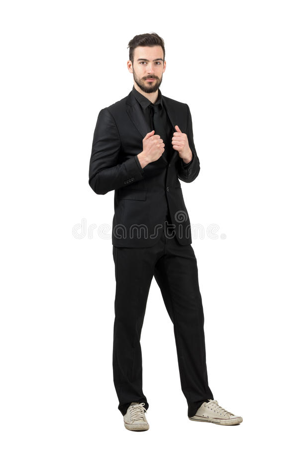 Trendy young bearded businessman wearing white sneakers and black suit royalty free stock image