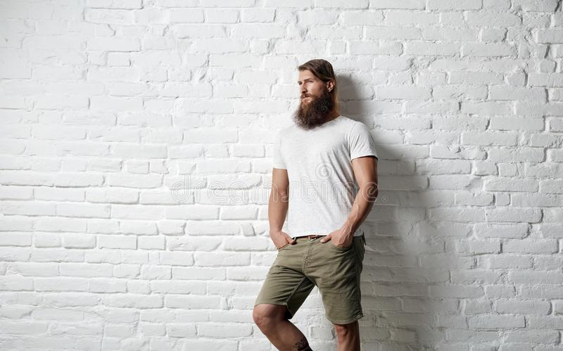 Trendy young bearded man against white brick wall stock images
