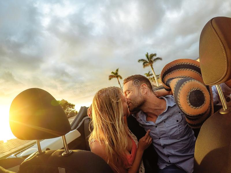 Trendy young couple having a tender moment in convertible car during their road trip - Happy romantic newlywed date kissing stock photos