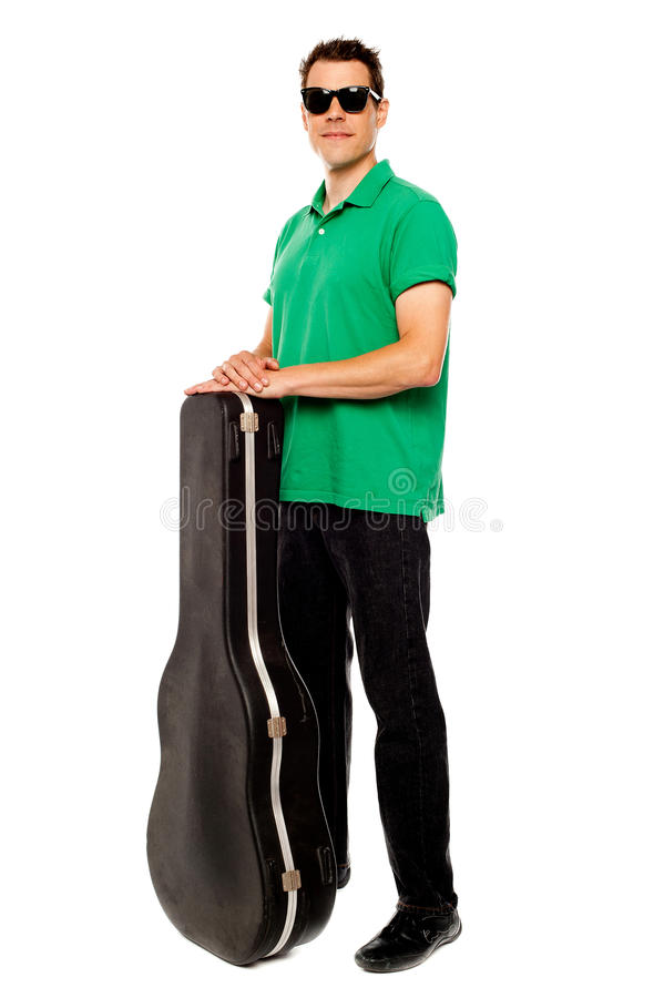 Trendy Young Man Posing With Guitar Case Stock Images