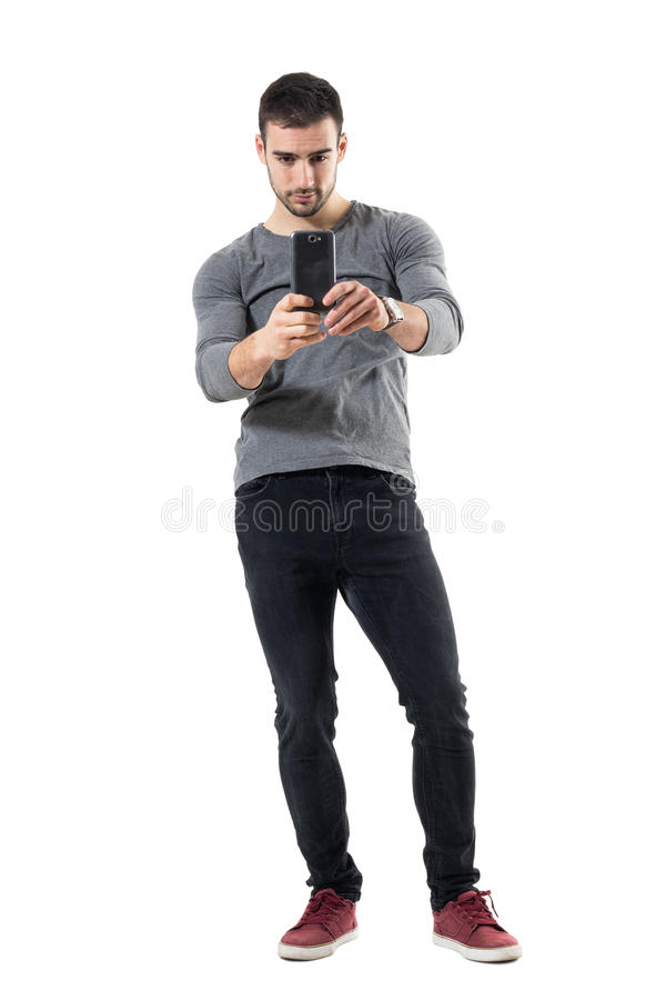 Trendy young man taking picture with mobile phone wearing red sneakers. Full body length portrait isolated on white studio background royalty free stock photos