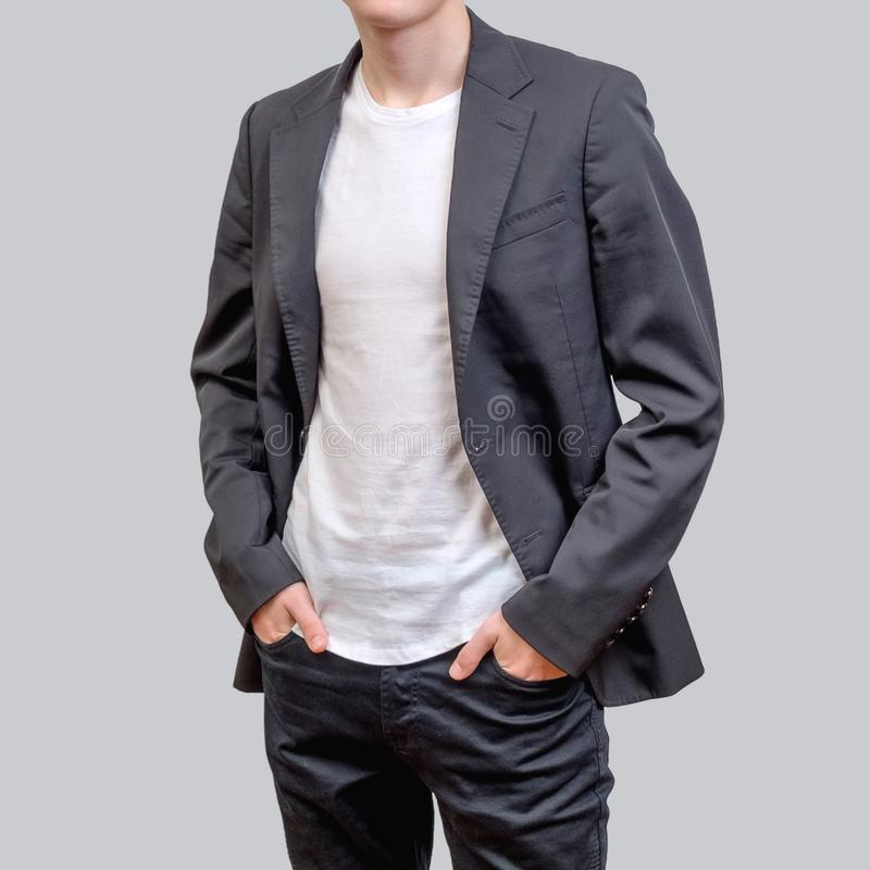 Trendy young man wearing grey blazer and dark jeans, standing against a grey background royalty free stock photos