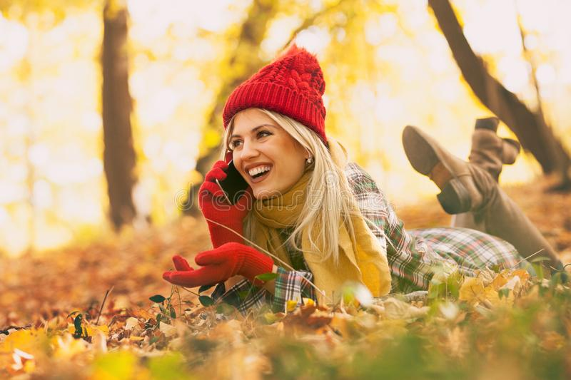 Trendy young woman in autumn park having call on her smartphone stock photography