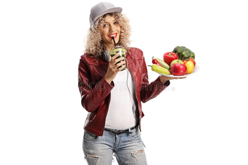 Trendy young woman holding a plate of fresh fruits and vegetables and a green smoothie stock photos