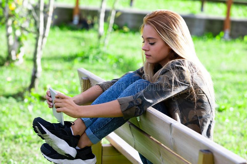 Trendy young woman relaxing on a wooden bench. Trendy young woman in jeans and sneakers relaxing on a wooden bench in a lush green garden or park with her feet royalty free stock images