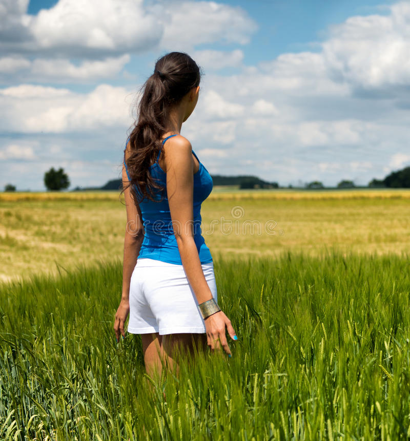 Trendy young woman standing in a green field. Trendy young woman standing in a green wheat field with her back to the camera looking out over scenic countryside stock image