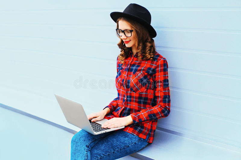 Trendy young woman working using laptop computer outdoors stock image