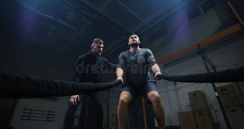 Trener nadzoruje młodego człowieka szkolenie z batalistyczną arkaną fotografia royalty free