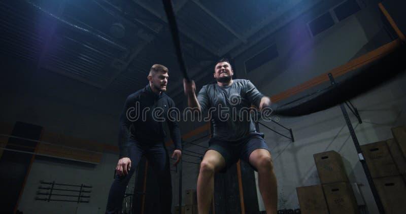 Trener nadzoruje młodego człowieka szkolenie z batalistyczną arkaną zdjęcia royalty free