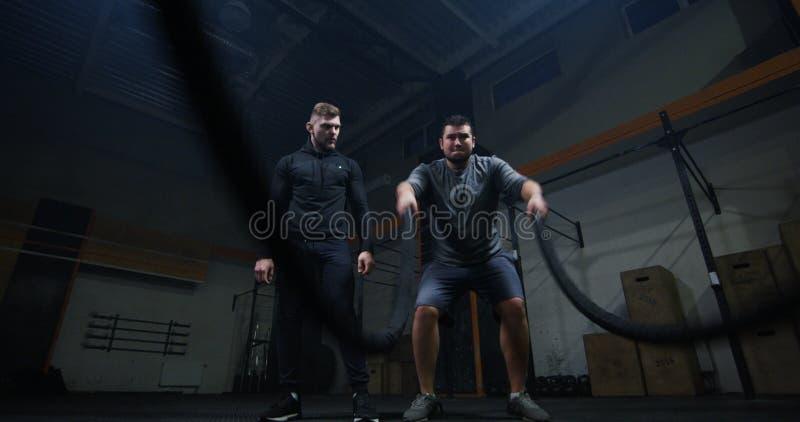 Trener nadzoruje młodego człowieka szkolenie z batalistyczną arkaną obrazy stock