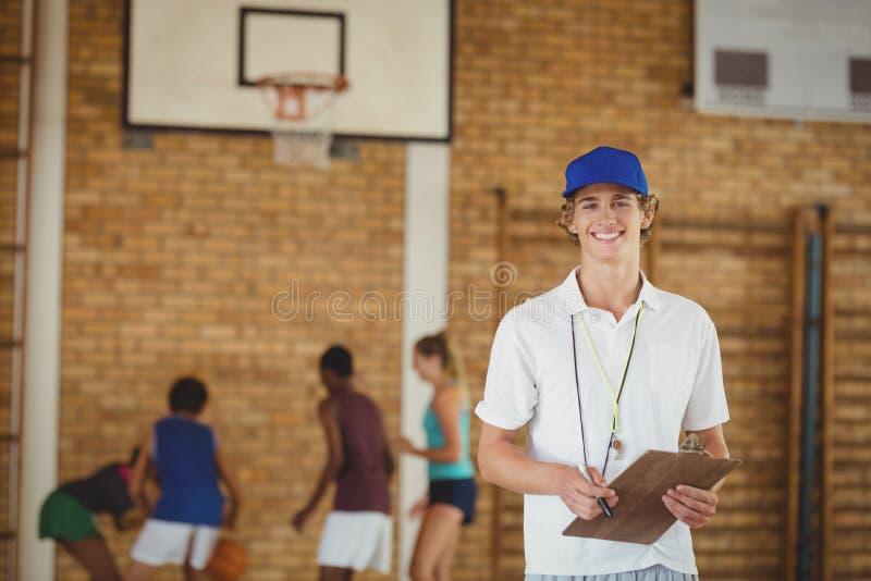 Trener ono uśmiecha się przy kamerą podczas gdy szkoły średniej drużyna bawić się koszykówkę w tle fotografia royalty free