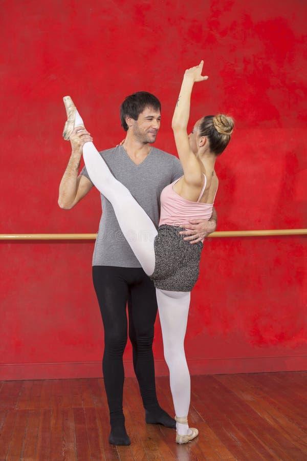 Trener Pomaga Żeńskiego Baletniczego tancerza W spełnianie rozłamu zdjęcia stock