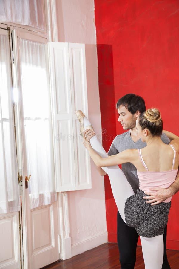 Trener Pomaga Żeńskiego Baletniczego tancerza W spełnianie rozłamu fotografia royalty free