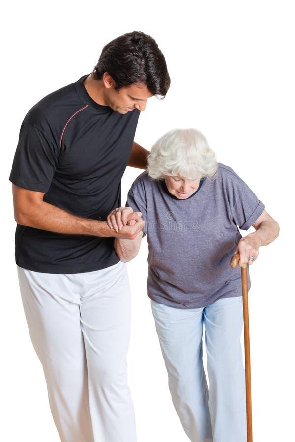 Trener Pomaga Starszego kobiety mienia odprowadzenie zdjęcie royalty free