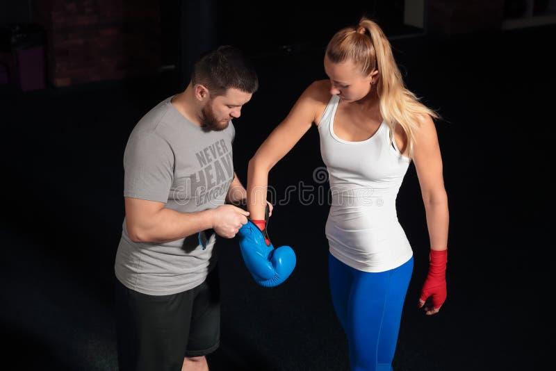 Trener stawia dalej bokserskich rękawiczek dziewczyny obrazy stock