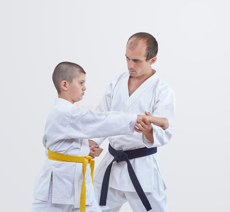 Trener z czarnym paskiem uczy karateka chłopiec z koloru żółtego paskiem bić cios obraz stock