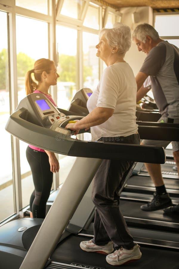 Trenera ćwiczenie pomaga starszej osoby pary Starsza para dalej zdjęcia royalty free