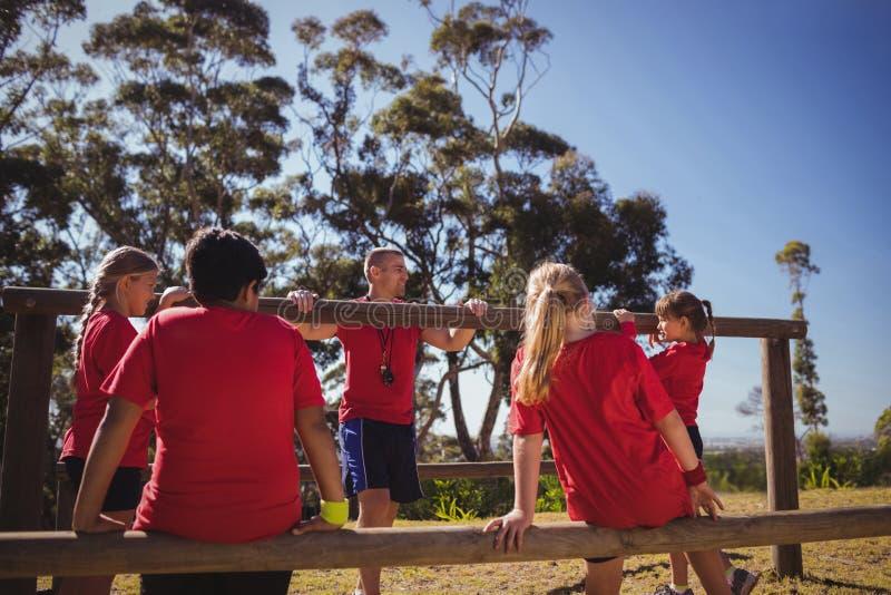 Trenera instruowania dzieciaki podczas przeszkoda kursu szkolenia fotografia royalty free