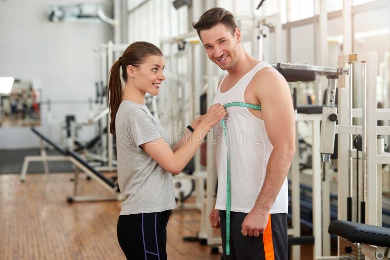 Trenera mierzyć obsługuje klatkę piersiową przy gym zdjęcia royalty free