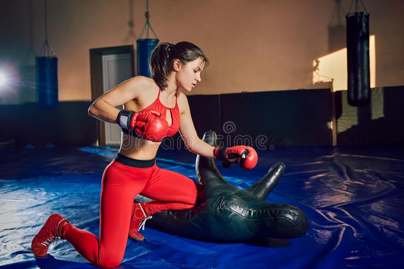 Trenes atléticos jovenes del combatiente de la muchacha en el gimnasio imagen de archivo