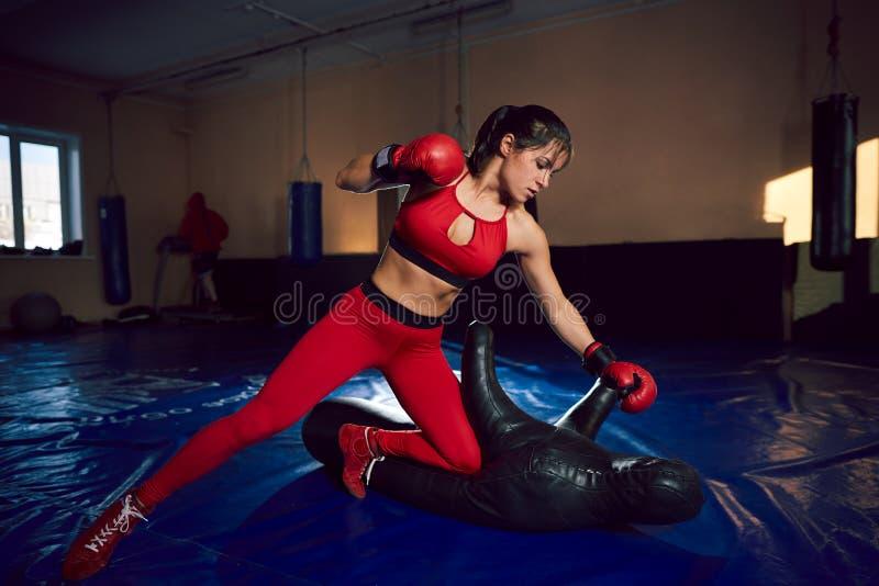 Trenes atléticos jovenes del combatiente de la muchacha en el gimnasio fotos de archivo libres de regalías