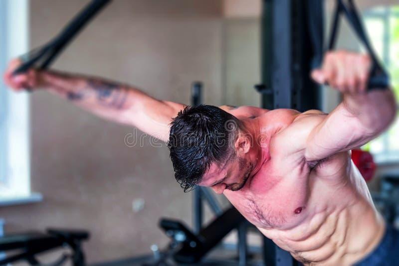 Trenes atléticos jovenes del hombre en el gimnasio cansado fotografía de archivo