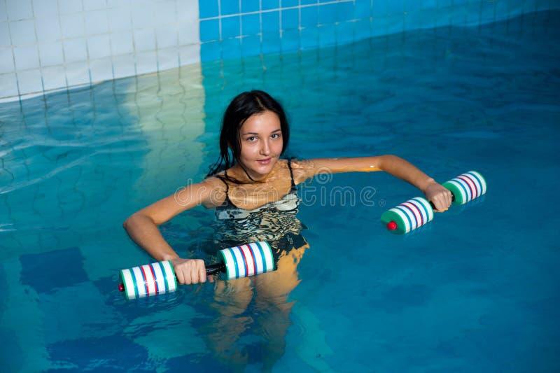 Trenes atractivos de la muchacha en aeróbicos del aqua imagen de archivo libre de regalías