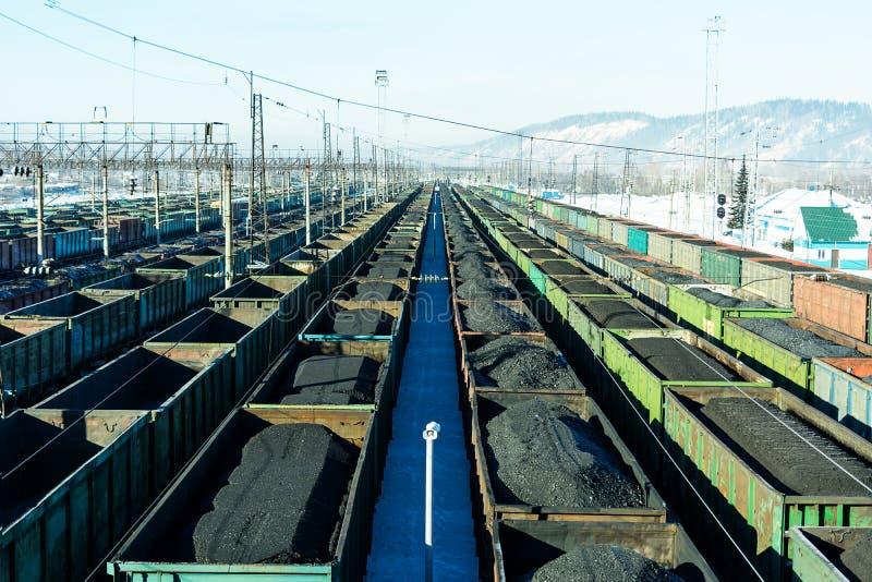 Trenes de carga con el carbón en la yarda que forma foto de archivo