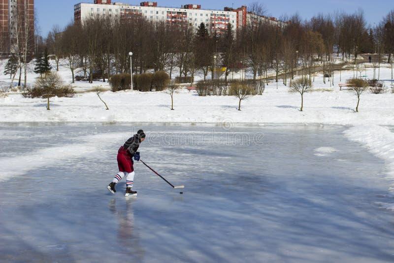 Trenes de un jugador de hockey en el hielo Una lavadora con un palillo en el lago imagen de archivo