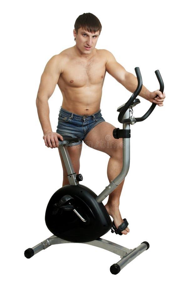 Trenes del hombre en la bicicleta del ejercicio imagen de archivo