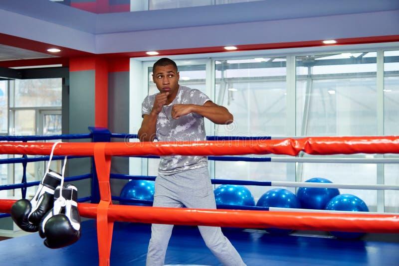 Treni di un giovane nel ring nella palestra fotografia stock libera da diritti