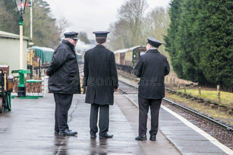 Treni a vapore inglesi e tre conduttori sul binario immagini stock